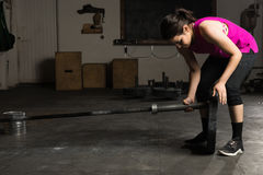 Getting ready to lift some weights. Active young woman setting up a barbell with some weights before working out in a gym Royalty Free Stock Photo