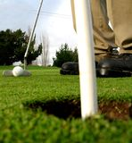 Getting ready to sink the putt. Shot of golfers shoes, iron & ball...ready to go for the putt Royalty Free Stock Image