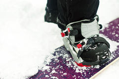 Getting ready to snowboard. Snowboard with secured binding strapped on the boot, getting ready to snowboard Stock Image