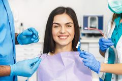 Getting Ready To Start Dental Examination. Smiling beautiful patient sitting in chair with dental purple bib, male dentist, in blue uniform and gloves, holding Stock Image