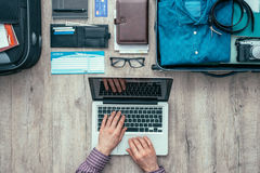 Getting ready for a trip. Traveler getting ready for a trip, he is packing his bag, planning a journey online and booking flights using a laptop, flat lay Royalty Free Stock Image