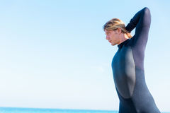 Getting ready for a wave ride. A young surfer putting on his wetsuit on the beach Royalty Free Stock Photography
