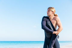 Getting ready for a wave ride. A young surfer putting on his wetsuit on the beach Royalty Free Stock Photos
