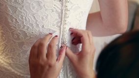 Getting ready for wedding ceremony. Mother or bridesmaid helping young bride to dress up bridal dress. Morning of young stock video footage