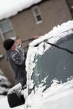 Getting Ready for Work. Man cleaning off snow & ice from automobile after a winter storm Royalty Free Stock Images
