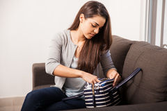 Getting ready for work. Cute brunette sorting things inside her purse before heading off for work stock image