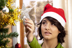 Getting ready for Xmas. A young brunette with a happy expression getting ready for Christmas by decorating her tree and wearing a Santa Hat Royalty Free Stock Images