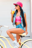 Getting refreshed. Carefree young women drinking juice and looking away while sitting on bicycle against the garage door royalty free stock photos
