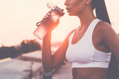 Getting refreshed. Close-up of beautiful young woman in sports clothing drinking water and looking tired while standing on the bridge with evening sunlight and Stock Photo