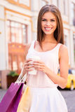 Getting refreshed after day shopping. Beautiful young smiling woman holding shopping bags and cup of hot drink while standing outdoors Stock Images