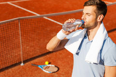 Getting refreshed after game. Thirsty young man in polo shirt and towel on shoulders drinking water while standing on tennis court royalty free stock photography