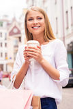 Getting refreshed before next store. Beautiful young smiling woman holding shopping bags and cup of hot drink while standing outdoors Royalty Free Stock Image