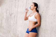 Getting refreshed after training. Beautiful young woman drinking water from the bottle while leaning at the concrete wall stock image
