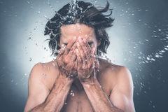 Getting refreshed. Young shirtless man washing face with water splashing around him Stock Image