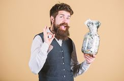 Getting rich. Rich businessman gesturing ok with money in glass jar. Bearded rich man with money cash. When become a. Rich man never trust a banker royalty free stock photo