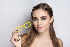 Getting rid of bad eyesight. Yellow paper eye glasses, conceptual idea getting rid of bad eyesight concept. Closeup portrait beautiful girl woman lady with Royalty Free Stock Images