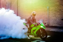Getting rid of an old tired. A motorcyclist does a burnout with an old tire on his street bike Royalty Free Stock Image