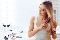 Getting rid of tangles. Beautiful young woman looking at her reflection in mirrorand brushing her long hair while sitting at the dressing table Stock Photography