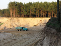 Getting of sand. Sand-pit, a truck drives sand, forest around Royalty Free Stock Photography