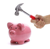Getting at savings. Hand with hammer about to smash piggy bank to get at savings Royalty Free Stock Images