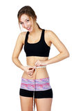 Getting in shape. Pretty, sporty and fit young woman in work out clothes happy over waist measurements, perfect for health issues Stock Image