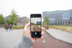 Getting the shot. A hand holding a Cell phone taking a picture in the city of Leiden, netherlands Royalty Free Stock Images