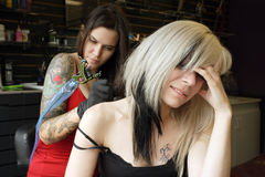 Getting a shoulder tattoo. A female tattoo artist applying her craft onto the back and arm of a female in her 30's. (Property release for tattoo artwork attached stock photo