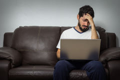 Getting some bad news by email. Headache, in pain. Bearded man with severe headache, worried. And looking at laptop. Bad news concept royalty free stock photos
