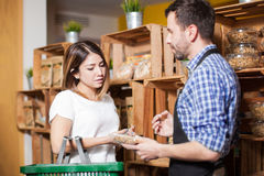 Getting some help from a store clerk. Cute brunette getting some assistance from a store clerk at a local grocery store royalty free stock photos