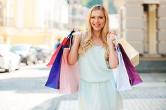 Getting some retail therapy. Happyyoung woman holding shopping bags and looking at camera while standing outdoors Stock Photo