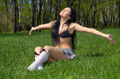 Getting the spring sunbath. Brunette getting getting spring sunbath, sitting on the green grass royalty free stock images