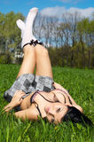 Getting the spring sunbath. Brunette getting spring sunbath, lying on the green grass royalty free stock images