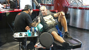 Getting a tattoo. Person in a chair getting a tattoo Stock Photos