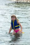 Getting There. Young girl wading out in relatively deep water looking to her destination Stock Photo