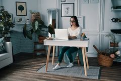 Getting things done. Beautiful young woman working using computer while sitting in home office stock image