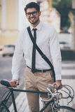 Getting to work. Cheerful young man in glasses looking at camera with smile and holding hand on his bicycle while standing outdoors Stock Image