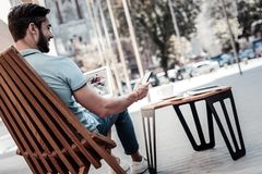 Smiling young man using smartphone while working in cafe Royalty Free Stock Images