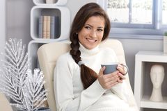 Getting warm at winter. Pretty smiling woman getting warm at winter with tea mug handheld, smiling looking away Stock Photography