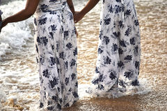 Getting wet at the beach. Two woman holding hands at the dege of surf getting the gowns wet Royalty Free Stock Image