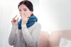 Portrait of diseased woman dripping her nose. Getting worse. Portrait young diseased woman using nasal drops while dripping her nose and looking away stock image