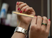 Getting your nails done. Woman files her nails by emery board from manicure set in a fashion salon Stock Photo