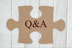 Q&A text on a cardboard puzzle piece. Getting your questions answered, Q&A text on a cardboard puzzle piece on weathered whitewash textured wood royalty free stock images