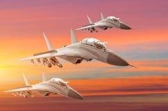 Getto di combattenti militare tre aerei del gruppo all'alta velocità, volante su nel tramonto del cielo Immagini Stock Libere da Diritti