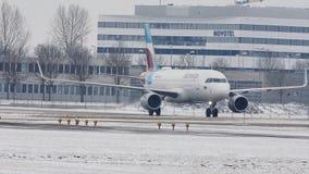 Getto di Eurowings Europa Airbus A320-200 OE-IQC al cuscinetto di sbrinamento sulla pista dell'aeroporto di Monaco di Baviera stock footage