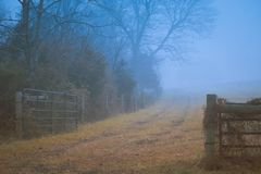 Gettysburg, PA/USA - Dezember 2018: Ein alter Bretterzaun entlang dem mystischen Schotterweg im Nebel Getrennt auf Weiß stockbilder