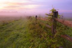 Gettysburg, PA /USA- Summer 2018. Sunrise over misty grassland with wooden fence in the foreground. royalty free stock photos