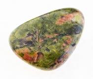 getuimelde unakite steen op wit stock afbeelding