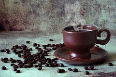 Geurige hete koffie in een mooie kleikop onder de verspreide koffiebonen stock afbeelding
