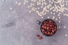 Geurige korrels van zwarte koffie in een zwart glas op een grijze concrete achtergrond stock foto's