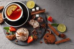 Geurige thee in een zwarte kop op een zwarte plaat met koekjes, citroen, kaneel en vruchten royalty-vrije stock foto's